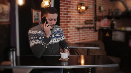elküldés : Portrait young happy attractive man sits use phone in cafe. Handsome man sitting with smartphone at the bar Stock mozgókép