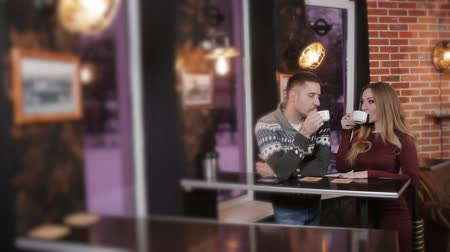 сплетни : Beautiful couple at the bar in a cafe drinking coffee and talking