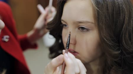 paleta : Makeup artist paint brush the eyes of the girl the teenager