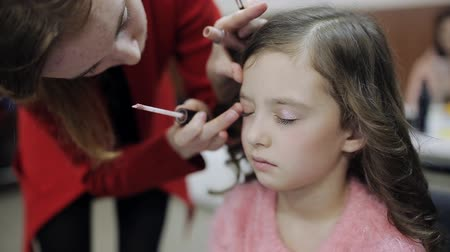 getting ready : master makeup artist paints the eyes of the little girl