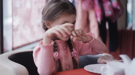 объяснять : Little girl in a cafe waiting for a tasty treat