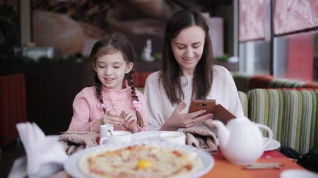 calabresa : Mom and her daughter in a pizzeria, take pictures on the smartphone pizza