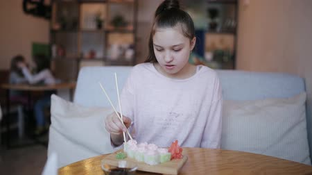 kaviár : Girl teenager eats sushi rolls in a cafe