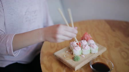 васаби : Close-Up Young Girl Eating Sushi with Chopsticks in a Japanese Restaurant