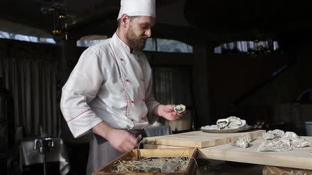 oysters : Chef in a luxury fish restaurant opens oysters on the table and puts them on a plate with ice Stock Footage