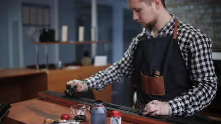 нож : Leather handbag craftsman at work in a workshop