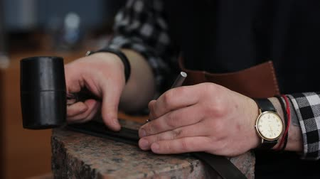 szewc : Working process of the leather belt in the leather workshop. Man holding crafting tool and working. He is placing billet to sturdy stand, fixing round knife on a mark and hitting with a small hammer