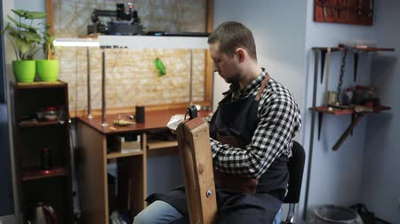 дубленый : male Tanner in his Studio working on the production of leather belt. The final stage, a man with a needle and thread makes the stitching