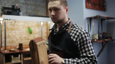 ручная работа : Working process of the leather belt in the leather workshop. Man holding crafting tool and working. He is placing billet to sturdy stand, fixing round knife on a mark and hitting with a small hammer