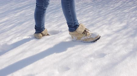 botas : Female Legs Wearing Black Snow Boots Walking Though Fresh Snow On A Winter Day