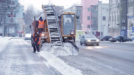 snow plow : Tractor cleaning the road from the snow. Excavator cleans the streets of large amounts of snow in city. Workers sweep snow from road in winter, Cleaning road from snow storm.