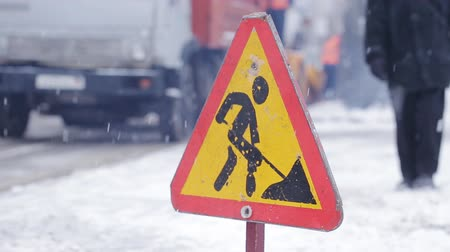 obnova : Close-up of the sign Road works, in the background the machinery removes snow from the roadside.