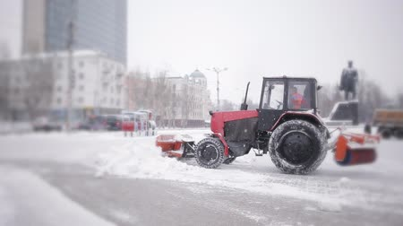 snow plow : The work of communal services in the winter. People and machinery are clearing the snow from the city