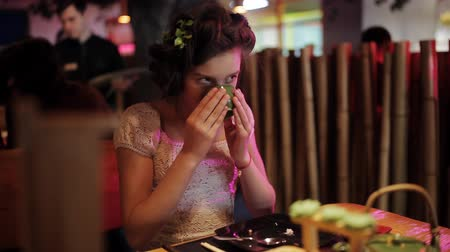 simmer : Girl teenager in a sushi restaurant, drinking green tea from a special tea Cup Stock Footage
