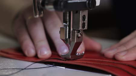 step : close up shot of the master hands, who uses a sewing machine to create stitches on a leather wallet, the needle slowly pierces the material