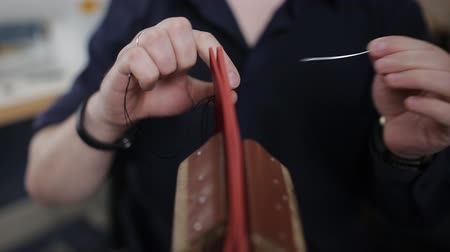мастер : Man creates a brown leather wallet with his own hands with a needle in the leather workshop, closeup Стоковые видеозаписи