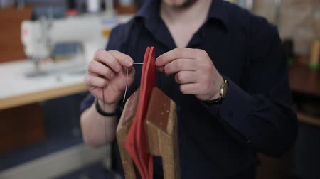 purse : Man creates a brown leather wallet with his own hands with a needle in the leather workshop