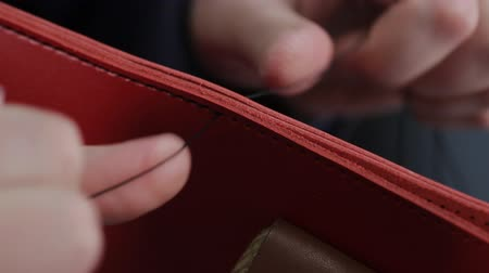 řemeslníci : Man creates a brown leather wallet with his own hands with a needle in the leather workshop, closeup Dostupné videozáznamy