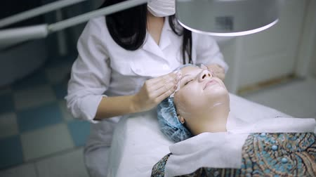 aydınlatmak : The cosmetologist in the beauty parlor sponges the mask off the face of the client Stok Video