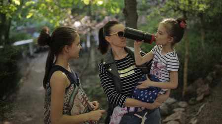 omzunda : Family vacation. Mother with two daughters, strolling through the Park. Stop to quench their thirst.