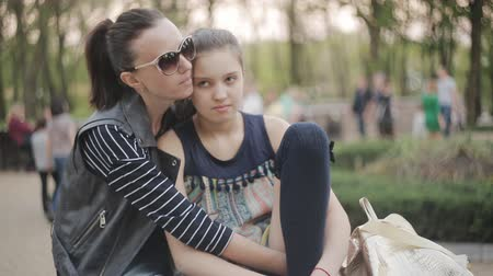рождение : Mother and daughter sit in park together and share a hug Стоковые видеозаписи