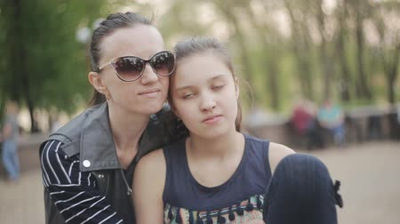crowded people : Mother and daughter sit in park together and share a hug Stock Footage