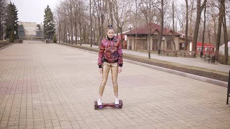 self driving : Sad girl rides an electronic scooter in an empty Park Stock Footage