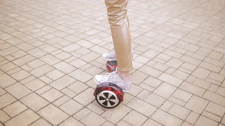 self balancing : Girl teenager spinning on smart scooter. Close-up of feet on a electronic scooter.