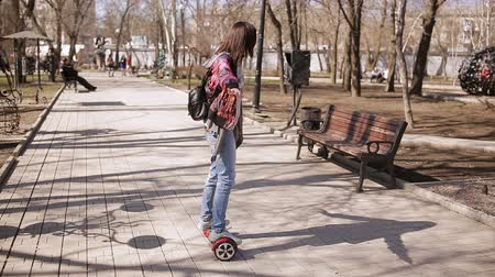 battery vehicle : A middle-aged woman learns to ride an electronic scooter. Stock Footage