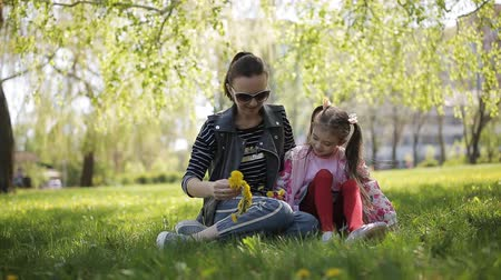 ткать : Mother with her daughter gather dandelions in the Park and weave a wreath of flowers