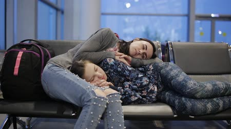 lugares sentados : The mother and daughter in the waiting room of the airport sleeping on chairs