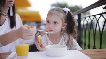 harmful : Mom feeds naughty girl soup in the restaurant outdoor