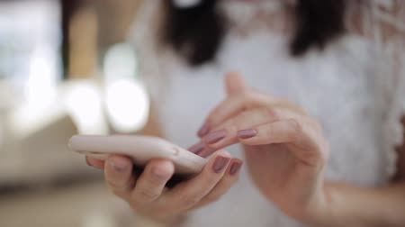 mms : Closeup of young woman hands typing sms scrolling pictures phone Stock Footage