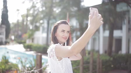 csak : Beautiful girl in sunlight makes a selfie on your smartphone