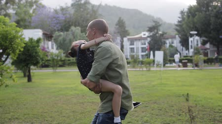проданный : Daughter jumping in the arms of his father, and he turns to her and laughs