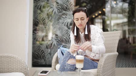 латте : Girl in the cafe in the fresh air sitting in a chair drinking latte from a glass Cup through a straw