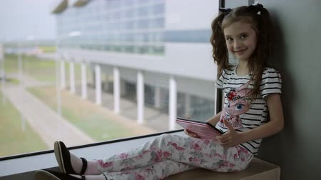 průchod : Child at the airport near the window playing a game on the tablet and waiting for time of flight