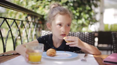 kruvasan : Adorable girl having breakfast at outdoor cafe. Adorable girl drinking fresh juice and eating croissant on terrace