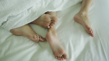 probudit se : Two pairs of legs of the happy family in bed under the coverlet - mother and baby
