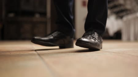 butterflies in the stomach : Closeup of male feet in leather shoes. A man waiting for a meeting worried and shifting from foot to foot