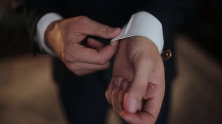 kravata : A young man in black suit adjusts his cufflinks of white shirt.