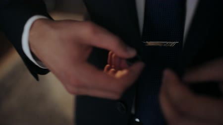 getting ready : Buttoning a jacket. Stylish man in a suit fastening buttons on his jacket preparing to go out. Close up