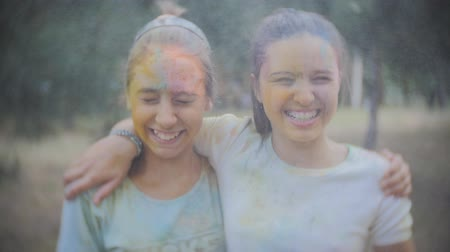 возбуждение : Two teenage girls smeared with colored powder Holi sprinkle water in the summer Park in Slow motion Стоковые видеозаписи