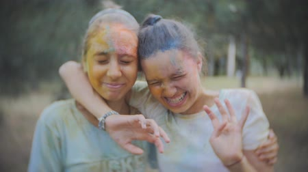 искренний : the water spray of two of teenage girls covered in Holi paint in the Park after Holi festival Стоковые видеозаписи