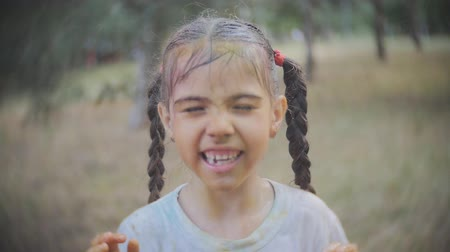 úmido : little girl smeared with colours of Holi laughs and enjoys the water splash in the face