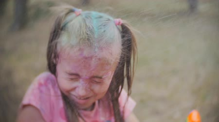 borrifador : little girl smeared with colours of Holi laughs and enjoys the water splash in the face
