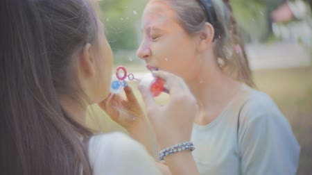искренний : Two girls soiled dry colors Holi laugh and blow bubbles