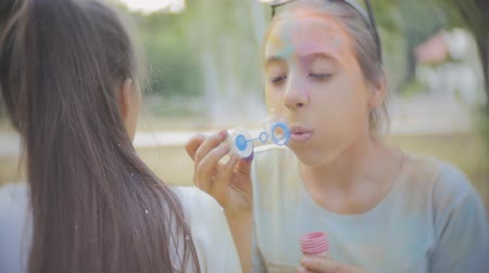 juntar : Two girls get dirty with dry colors Holi blow soap bubbles