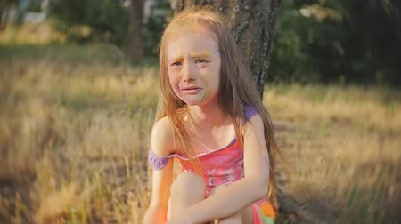 little finger : Little girl smeared with colours of Holi crying sitting in a tree Stock Footage