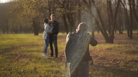 ele geçirmek : Professional photographer photographing young loving couple on nature in the Park.